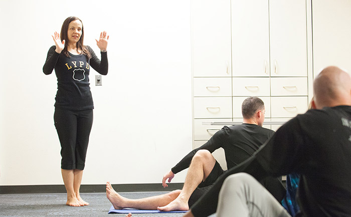Instructor Jeanne Douglas, of Yoga Indigo in Bend, leads a patrol unit in a yoga class. In 2015, the department commissioned local yoga instructors such as Douglas to lead four one-hour classes a week with the goal of injury prevention.